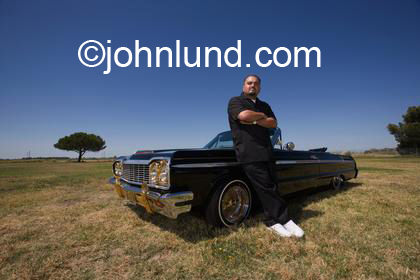 A serious looking hispanic man looking down at the camera and leaning on his low rider cherry, convertible chevy impala. Tracy California.